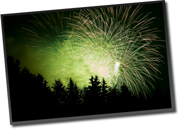 Large, green fireworks display over a pine forest hillside.