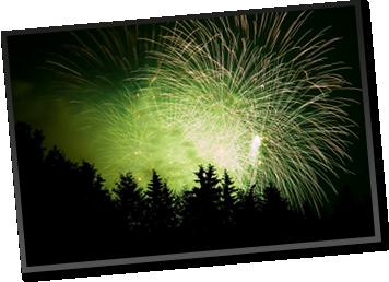 Large, green fireworks display over a pine forest hillside.