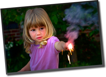 A little girl, fascinated,  holds a sparkler in her yard.